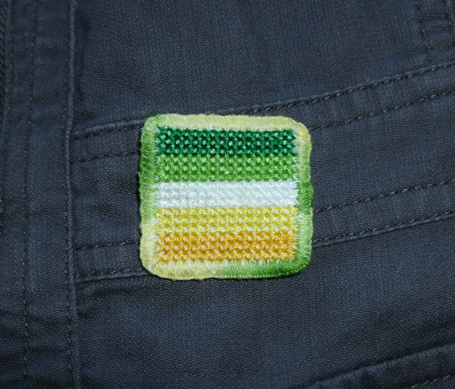 A square pride patch attached to the front panel of a grey jacket. The patch is made of five stripes of coloured thread cross-stitched onto aida cloth, the edges embroidered with a tight blanket stitch done in an embroidery floss that darkens and fades from pastel yellow to a grass green. The five cross-stitched stripes are sewn in the colours of the allo-aro pride flag: dark green, light green, white, yellow, gold.