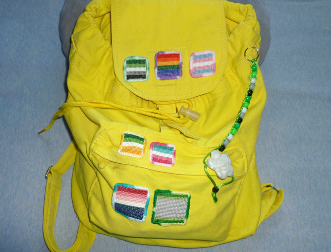 A yellow canvas backpack sitting on a light blue sheet. The backpack is covered with multiple square cross-stitched patches in the designs of various pride flags. Pride flags include aromantic, gay/rainbow/queer, trans, allo-aro, abrosexual, nebularomantic and arovague. The patches are all edged with embroidery in variegated threads shifting between two colours or a lighter and darker shade of the same colour.