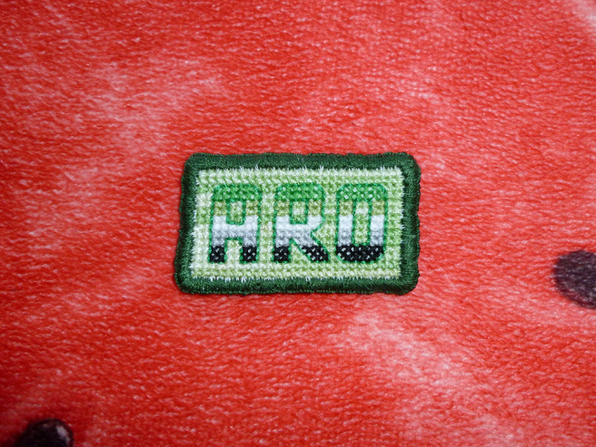 "A rectangular pride patch sitting on a bright red pillow. The patch features the word ""ARO"" embroidered in the dark green, light green, white, grey and black of the aromantic pride flag, outlined in bright green back-stitch. The text sits in front of a colour-shifting green background and the whole patch is edged in dark green thread."