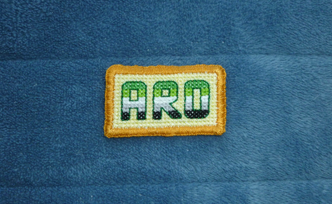 "An embroidered, cross-stitch patch sitting on a blue microfibre blanket. The patch is rectangular, featuring the text ""ARO"" sewn in the colours of the dark green/light green/white/grey/black pride flag against a pale yellow cross-stitched background and a gold hand-embroidered border"