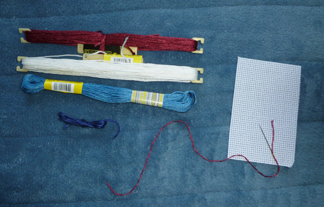 Photo of a small swatch of white aida in 14 count; three skeins and one scrap of embroidery floss in the maroon, white, turquoise and dark blue of the nebulaquoi flag; and a tapestry needle threaded with two strands of the maroon floss.