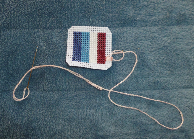 Four blanket stitches in a pale pink floss, the three strands threaded on a sharp embroidery needle, encircle the strip of raw white aida beside the maroon stripe cross stitch. The stitches are immediately beside each other and the row of maroon cross stitches, showing no flashes of the white aida underneath. A small loop is arranged at the base of the thread where it extends from the patch; the needle has been threaded through it.