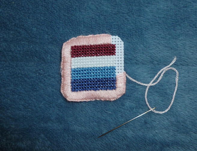 The pink floss blanket stitch border now encloses three and a half sides of the patch, leaving one bare white corner.
