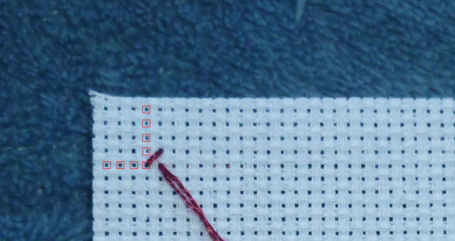 Close up photo of a piece of white aida, top left-hand corner, with one diagonal stitch worked in maroon thread. Small red boxes have been placed around the holes in the weave, counting down five boxes from the horizontal edge and four boxes in from the vertical edge.