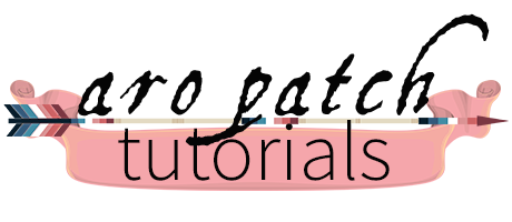 Text Aro Patch Tutorials in black lettering above an image of an arrow decorated with nebularomantic pride colour banding. A pink banner sits behind the word Tutorials.