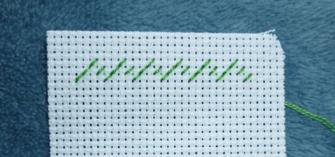 Close up photo of a piece of white aida, top left-hand corner, with a row of back stitches in green floss shaped like a series of mountain peaks. All stitches are sewn on the diagonal and facing in the same direction--left to right. This forms the row of half stitches waiting for the stitches to cross them to form a true zigzag line.