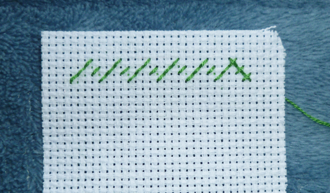Close up photo of a piece of white aida, top left-hand corner, with a row of back stitches in green floss shaped like a series of mountain peaks. All stitches are sewn on the diagonal and facing in the same direction--left to right. This forms the row of half stitches. Three stitches on the end have been crossed over with a line of back stitch in the opposite direction, forming three crosses.
