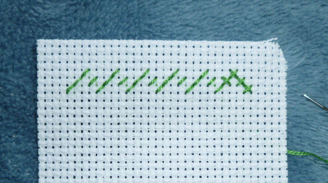 Close up photo of a piece of white aida, top left-hand corner, with a row of back stitches in green floss shaped like a series of mountain peaks. All stitches are sewn on the diagonal and facing in the same direction--left to right. This forms the row of half stitches. Four stitches on the end have been crossed over with a line of back stitch in the opposite direction, forming four crosses.