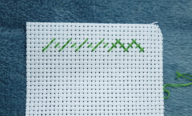 Close up photo of a piece of white aida, top left-hand corner, with a row of back stitches in green floss shaped like a series of mountain peaks. All stitches are sewn on the diagonal and facing in the same direction--left to right. This forms the row of half stitches. Eight stitches on the end have been crossed over with a line of back stitch in the opposite direction, forming eight crosses.