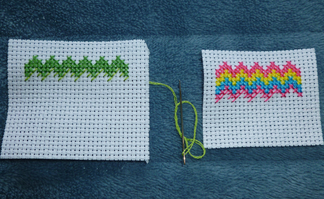 Close up photo of two pieces of white aida showing two different zigzag patches in progress of sewing. The left-hand patch has a row of zigzags three stitches high in dark green, with a half row of light green underneath. The right-hand patch has a row of pink, yellow and blue zigzags two stitches high, with a second pink stripe in progress sewn underneath the blue one.