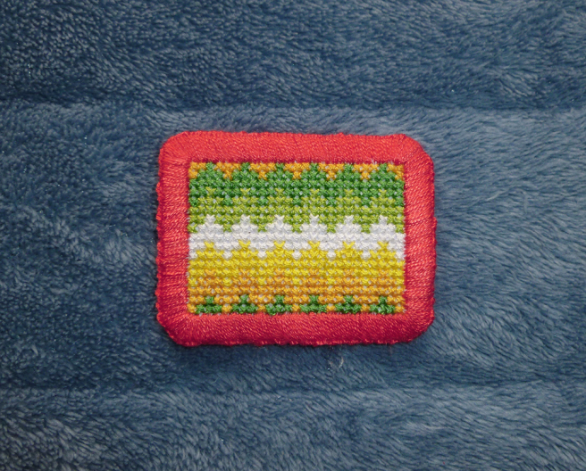 Close up photo of a completed allo-aro zigzag pride patch sitting on a blue microfibre blanket. The flag has horizontal zigzag stripes, each three stitches high, in dark green, light green, white, yellow and gold. The valleys at the top of the patch have been filled in with the bottom stripe's gold; the peaks at the bottom of the patch have been filled in with the top stripe's green. The patch is finished with a red-orange thread border.