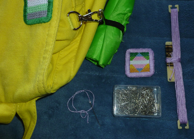 Photo of the edge of a yellow canvas bag; a square transgender/allo-aro patch edged in lilac; a sharp needle threaded with a doubled strand of the lilac floss; the skein of lilac floss; and a small box of silver sequin/applique pins. The patch features the dark green, light green, white, yellow and gold stripes of the allo-aro flag framing a diamond of the blue, pink, white, pink and blue stripes of the transgender flag.