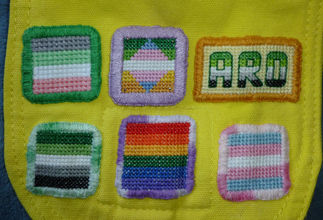 Photo of the top flap of a yellow canvas bag, featuring two rows of cross stitch patches. Top row shows idemromantic flag, trans/alloaro flag and aro text patches; bottom row shows aro, gay/rainbow/LGBTQIA+/trans flag patches. The trans/allo-aro patch has only been pinned to the bag with four small silver pins sitting in the corners of the patch.