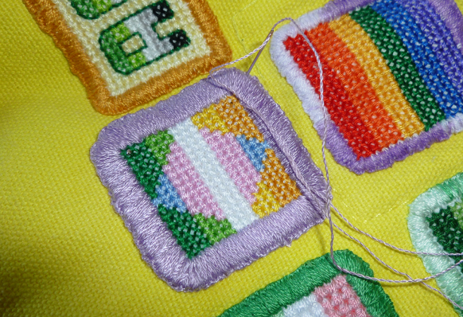 Close up photo of the trans/allo-aro patch. The beginning of a stitch has been sewn from the inside of the patch's edging, the needle inserted into the patch and bag beneath, waiting to be pulled through to complete it. The patch's border is composed of many threads sewn close together, with most of the threads angled in the same direction. A few new stitches, fastening the patch to the bag, don't quite follow the direction of the earlier ones and are more visible.