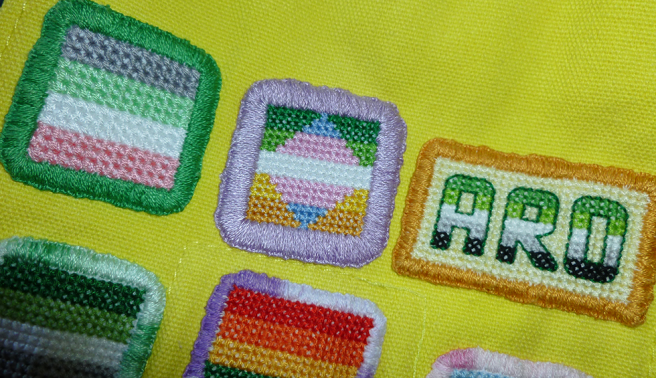 Photo of the top flap of a yellow canvas bag, featuring two rows of cross stitch patches. Top row shows idemromantic flag, trans/alloaro flag and aro text patches; bottom row shows aro, gay/rainbow/LGBTQIA+/trans flag patches. The bag is creased in the centre and the patches are sewn on at not-quite-straight angles. It looks similar to the earlier photo with the patch pinned in place, only without the pins.