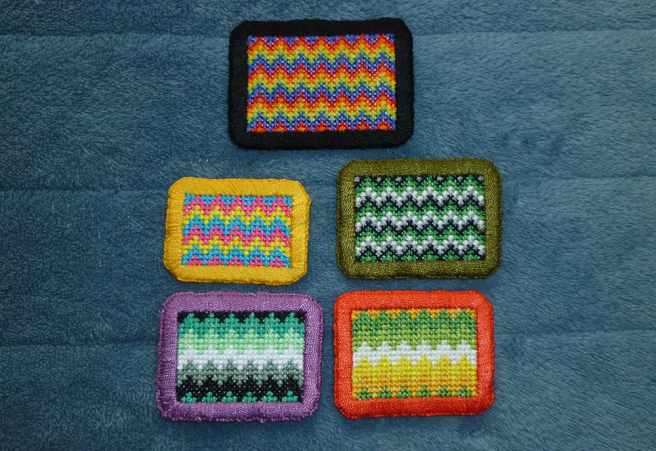 Five handsewn cross stitch patches sitting on a blue microfibre blanket. Patches all feature a horizontal zigzag stripe pattern. Patches from top to bottom include: gay/rainbow/LGBTQIA+ with repeated stripes and a black border; pansexual with repeated stripes and a gold border; aromantic with repeated stripes and an olive border; aromantic with a purple border; and allo-aro with a red-orange border.