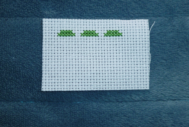A swatch of white aida sitting on a blue microfibre blanket. Three sections of green cross stitch, spaced two blocks apart, have been sewn over two rows near the swatch's top, forming the eventual tops of the letters A, R and O.