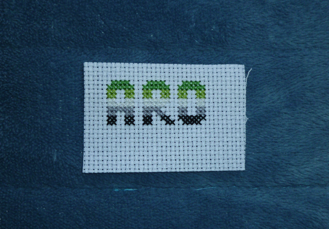 "A swatch of white aida sitting on a blue microfibre blanket. The word ""aro"" has been cross stitched onto the fabric in block type, the letters sectioned into the dark green, light green, white, grey and black stripes of the aro pride flag."