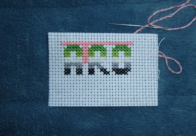 "A swatch of white aida sitting on a blue microfibre blanket. The word ""aro"" has been cross stitched onto the fabric in block type, the letters sectioned into the dark green, light green, white, grey and black stripes of the aro pride flag. Two blocks of white space exists between each letter, with more space left above and below them; a sewing needle threaded with pink floss is starting to fill in the black spaces around the lettering."