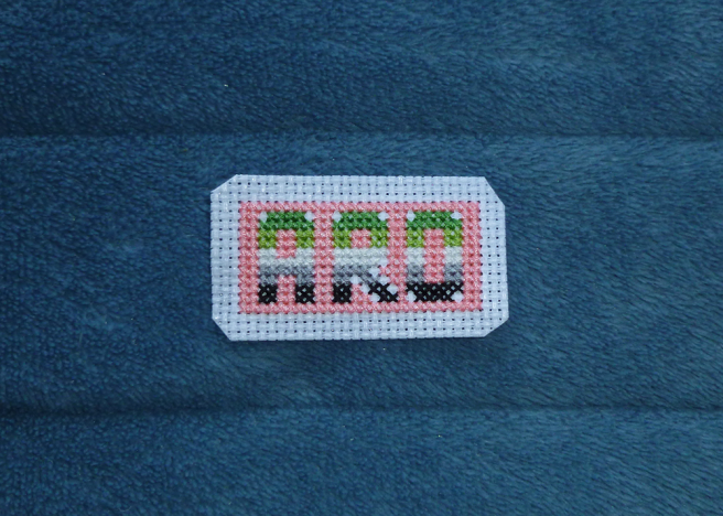 The aro text patch now has a pink background, the edges trimmed back for the edging. Small odd blocks of white aida have been left bare around places where the letters will be rounded off, waiting for the outline back stitch.