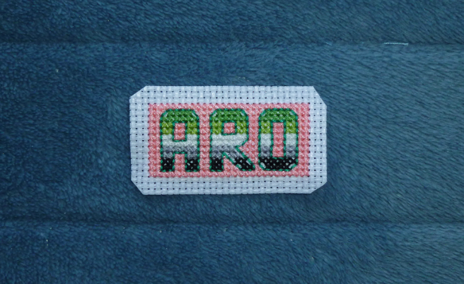 A dark green back stitch now frames the letters, letting them stand out even more against the pink background. Angled back stitch now cuts across the blocks left empty when filling in the background, leaving a very small gap in either corner.