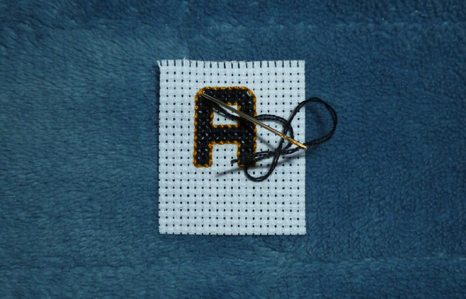 "A swatch of white aida sitting on a blue microfibre blanket. A block letter ""A"" is cross stitched on the aida in black floss and outlined in gold-brown, the top corners of the ""A"" rounded. The fabric is shown with the needle piecing the fabric underneath the diagonal gold outline stitch for the left-hand corner, hiding the end of the stitch once needle and floss has been pulled through."