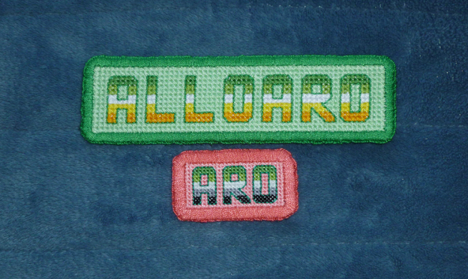 "Two cross stitch text patches sitting on a blue microfibre blanket. Top patch is larger with the text ""alloaro"" stitched in alloaro flag stripes on a green background with a green border. Bottom patch is smaller with the text ""aro"" stitched in aromantic flag stripes on a pink background with a pink border."