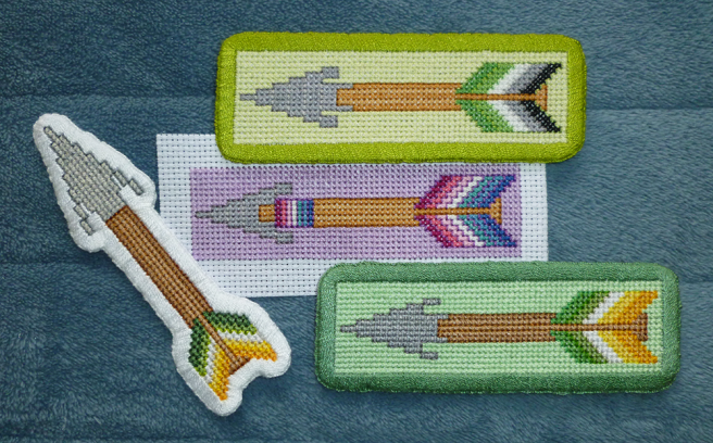 A collection of arrow patches, finished and in progress, sitting on a blue microfibre blanket. All patches have a grey triangular arrowhead, brown or tan shaft, and fletching coloured in the stripes of a pride flag. One rectangular patch has aromantic flag fletching on a light green-yellow background with a grass green border; one rectangular patch has allo-aro flag fletching on a light mint background with a darker mint border. One patch, unfinished with raw aida edges, has the nebularomantic flag on a purple background. The last patch, an allo-aro arrow, is cut around the shape of the arrow and finished in a thick white border.