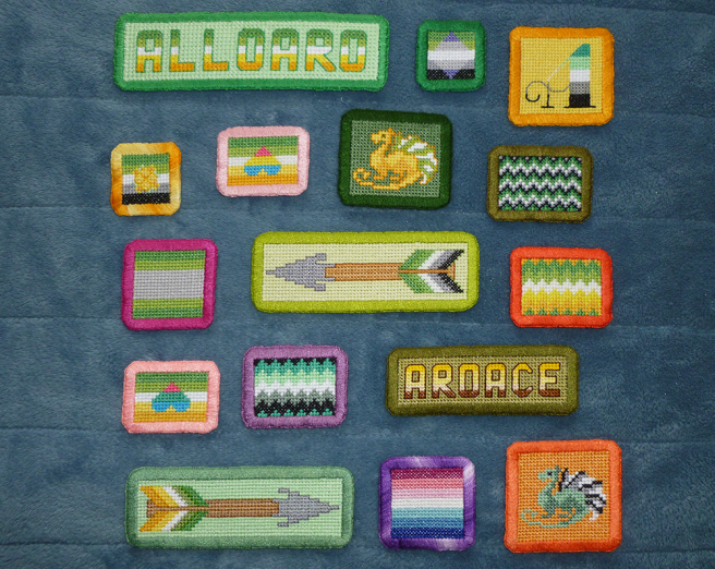 """An assortment of cross stitch patches with wide hand-embroidered borders in rectangluar and square shapes. Patches include various aromantic-spectrum flags in straight and zigzag lines, text patches """"alloaro"""" and """"aroace"""", arrow patches, patches with pan/ply hearts atop the allo-aro flag, dragon patches in flag colours and a calligraphic style letter A in aro colours."""