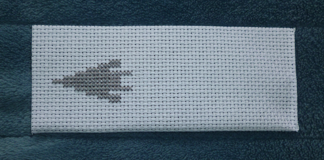 A rectangular white aida swatch sitting on a blue microfibre blanket. A grey arrowhead--an elongated triangle--has been stitched onto the aida on the left-hand side of the fabric.