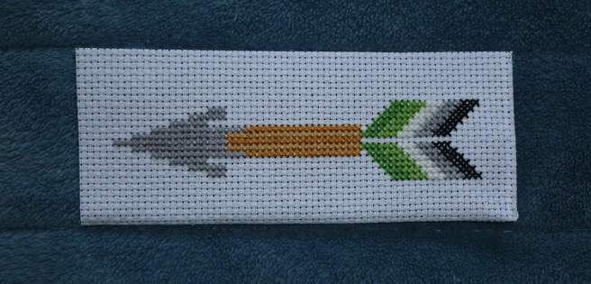 A rectangular white aida swatch sitting on a blue microfibre blanket. A grey arrowhead--an elongated triangle--has been stitched onto the aida atop a tan shaft, sewn in alternating stripes of dark and light. Behind the shaft sits two sections of fletching sewn in the five dark green/light green/white/grey/black stripes of the aromantic pride flag.