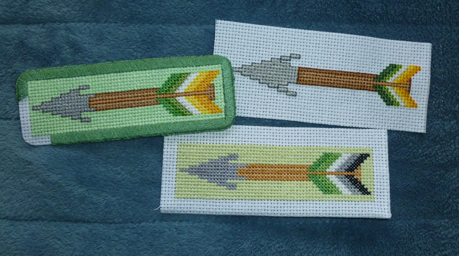 Three in progress patches, sitting on a blue microfibre blanket. All patches have a grey triangular arrowhead, brown or tan shaft, and fletching coloured in the stripes of a pride flag. One rectangular patch has aromantic flag fletching on a light green-yellow background and no back stitching; one rectangular patch has allo-aro flag fletching on a light mint background with a darker mint border, incomplate. The last patch, an allo-aro arrow, has no background and is sewn on plain white aida.