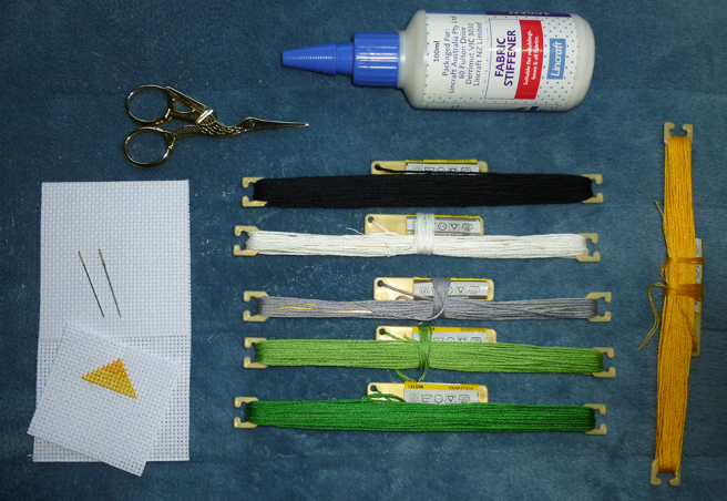A photo, taken on a blue microfibre blanket, of various needlecraft materials: floss in aro pride colours, gold embroidery scissors, Lincraft branded fabric stiffener, white aida swatches and sewing needles.