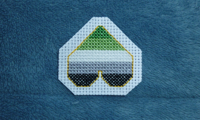 A photo, taken on a blue microfibre blanket, of an upside-down cross stitch heart patch in the dark green/light green/white/grey/black stripes of the aromantic pride flag, outlined in gold backstitch. The aida around the patch has been trimmed to resemble a squared-off heart shape.