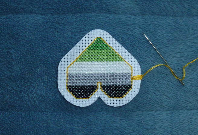 A photo, taken on a blue microfibre blanket, of an upside-down cross stitch heart patch in the dark green/light green/white/grey/black stripes of the aromantic pride flag, outlined in gold backstitch. The aida around the patch is now rounded off into curves around the points and swells of the heart, and the first few stitches of a gold-coloured buttonhole border are visible on the right side of the patch.