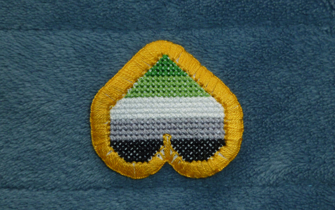 A photo, taken on a blue microfibre blanket, of an upside-down cross stitch heart patch in the dark green/light green/white/grey/black stripes of the aromantic pride flag, outlined in gold backstitch. The patch is trimmed with a gold buttonhole border, but a few white gaps of aida peek through the stitching, especially around curves and between the swells of the heart.