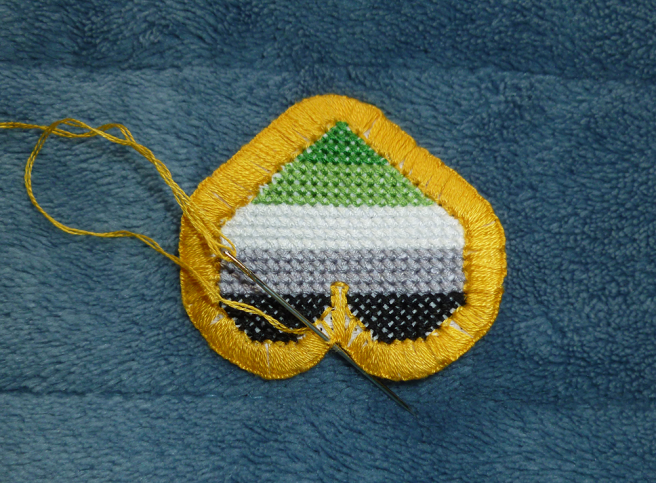 A photo of the previous aromantic heart patch. The patch is now trimmed with a gold buttonhole border, but a few white gaps of aida peek through the stitching, especially around curves and between the swells of the heart. A needle is shown with the thread coming up from the inside edge of the patch and going down behind the twisted edge of the buttonhole stitches on the outside.