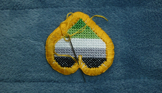 Another photo of the same heart patch, this time with more of the holes in the edging filled. A needle is shown with the thread coming up from the inside edge of the patch and going down underneath the cluster of stitches sitting between the swells of the heart.