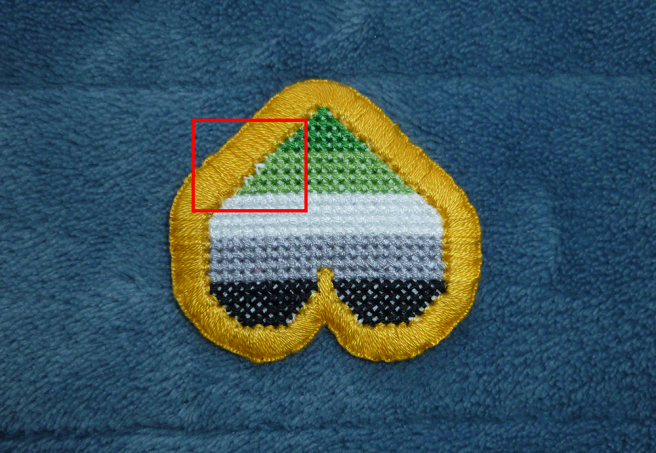 Another photo of the same aromantic heart patch, the gold buttonhole edging now complete. A red square outlines a section of the patch where the backstitch outline has been caught underneath the edging, leaving a bare hole of white aida.