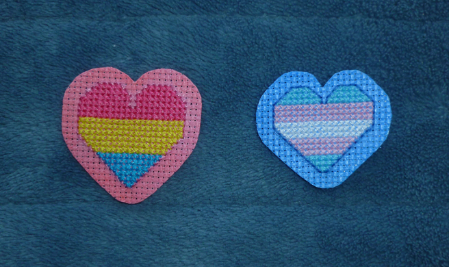 A photo, taken on a blue microfibre blanket, of a pansexual and a transgender heart patch, both sewn rightside up. Both hearts have been sewn onto aida coloured pink and blue, respectively, with graphic markers. The aida has been trimmed around the heart, leaving a wide border of coloured fabric.