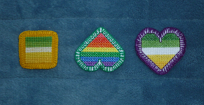 A photo, taken on a blue microfibre blanket, of three patches. One allo-aro patch is square and sewn on gold aida; a rainbow heart patch, upside down, is sewn on white aida; and an allo-aro heart patch is rightside up and sewn on white aida. The square patch is framed by two rows of backstitch and one of blanket stitch; the rainbow heart is framed by green blanket stitch, the stitches open to show the aida between; the allo-aro heart is framed by purple blanket stitch, the stitches thick on the border's outside edge and thin on the inside.