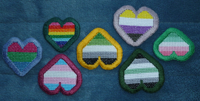 A photo, taken on a blue microfibre blanket of an assortment of pride-themed cross stitched heart patches, all with borders in thick buttonhole stitch. Hearts shown, sewn both upside down and rightside up, include rainbow, the gold-bordered aromantic test patch of this tutorial, abro, agender, p(o)ly, trans and non-binary flags.