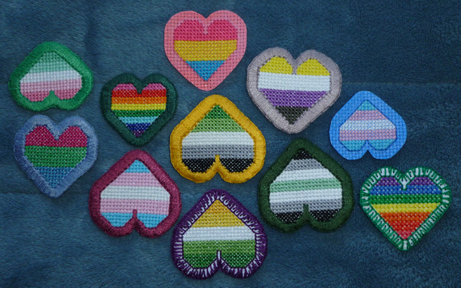 A photo, taken on a blue microfibre blanket of an assortment of pride-themed cross stitched heart patches, all with borders in thick buttonhole stitch, open blanket stitch or dyed aida. Hearts shown, sewn both upside down and rightside up, include rainbow, aro, allo-aro, abro, agender, pan, p(o)ly, trans and non-binary flags.