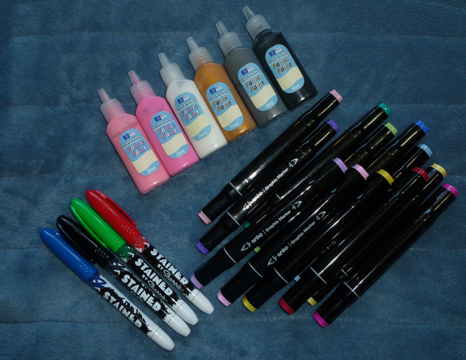 A photo, taken on a blue microfibre blanket, of various craft materials: Birch fabric paint in small plastic squeeze bottles, Stained by Sharpie fabric markers, black Anko graphic markers.