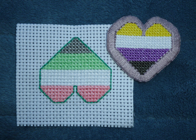 A photo, taken on a blue microfibre blanket, of an idemromantic heart patch, sewn upside down and on an uncut swatch of white aida. It sits beside a finished non-binary heart patch, sewn rightside up and bordered in mauve. The pattern is identical for both save the colours, but the idemromantic heart is bigger than the non-binary heart.