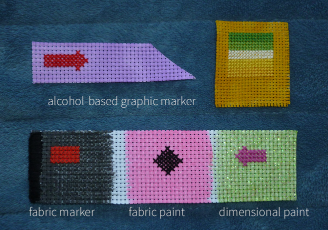Three coloured aida swatches sitting on a blue microfibre blanket. The top two swatches have been coloured purple and gold with alcohol-based graphic markers; the bottom swatch has been coloured in sections with a black fabric marker, pink fabric paint and glittery green dimensional fabric paint. Test stitches in squares, rectangles and arrows sit atop the coloured sections.