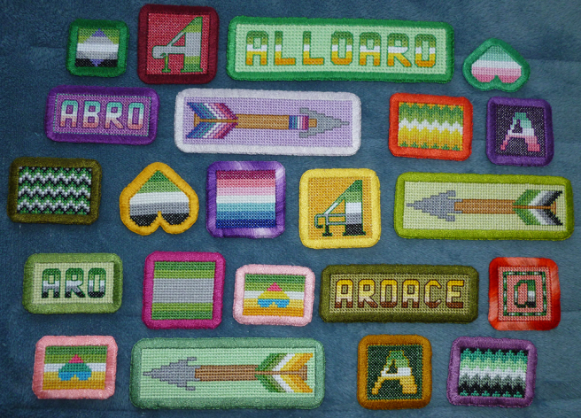 "An assortment of cross stitch patches with wide hand-embroidered borders in rectangluar and square shapes. Patches include various aromantic-spectrum flags in straight and zigzag lines, text patches ""aro"", ""abro"", ""alloaro"" and ""aroace"", arrow patches, patches with pan/ply hearts atop the allo-aro flag, heart-shaped patches and the A in aro, abro and allo-aro colours."