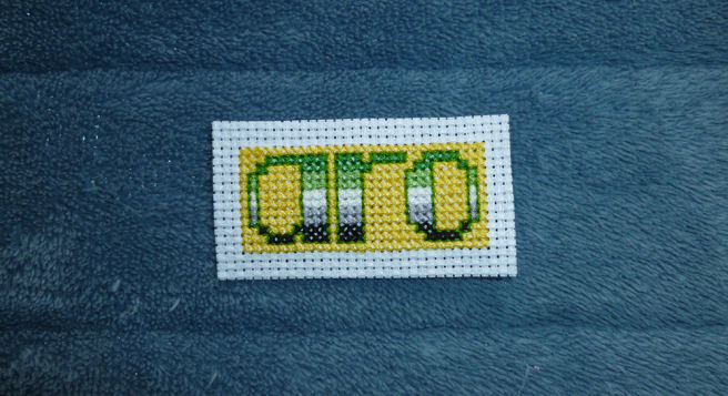 "A rectangular cross stitch patch in progress, sitting on a blue microfibre blanket. The patch bears the text ""aro"" in lower-case letters striped in the dark green/light green/white/grey/black of the aromantic pride flag on a yellow background. White untrimmed, unfinished aida frames the patch."