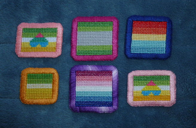Six cross-stitched patches sitting on a blue microfibre blanket. Four are square-shaped simple horizontally-striped pride flags with a contrasting embroidered border: arovague (green/grey) with dark pink, autistic aro (reds/yellow/blues) with dark blue, nebularomantic (pinks/white/blues) with purple and allo-aro (greens/white/yellow/gold) with orange. Two are rectangles featuring the allo-aro flag and a light or peach pink border, with a small upside-down heart in the centre. One patch has the heart stitched in pansexual colours; the other has polysexual colours.