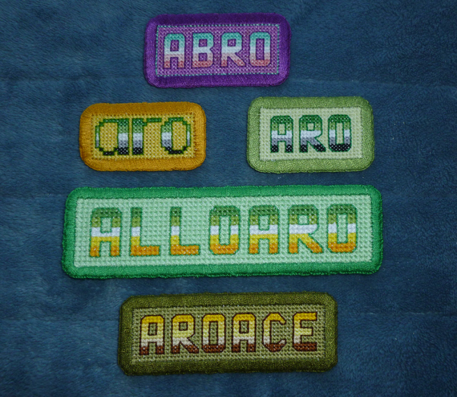 "Five cross-stitched patches sitting on a blue microfibre blanket. Each are a rectangle bearing text stitched in the flag coloured stripes against a solid-coloured background and a matching embroidered border. From top to bottom"" ""abro"" in abro colours and block capitals with a dark purple background; ""aro"" in green/white aro flag colours and lower case letters with a yellow/gold background; ""aro"" in green/white aro flag colours and block capitals with a light green background; ""alloaro"" in yellow/gold allo-aro flag colours and block capitals with a mint background; and ""aroace"" in yellow/brown angled aro-ace block capitals with an olive background."